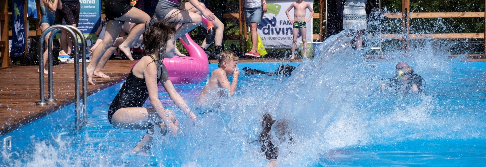 Dziecko skaczące do wody w basenie letnim. Drewniany podest i błękitna rozpryskująca się woda.