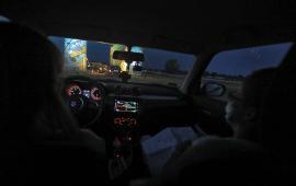 Osoby w maseczkach siedzą w samochodzie, który wjeżdża na teren festiwalu Auto Skyway