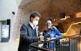 Fernando Menic robi notatki w czarnym notesie opartym na balustradzie w hallu Jordanek. Obok Stoi tłumaczka