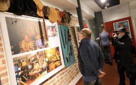 Dwóch mężczyzn ogląda eksponaty na wystawie poświęconej Tony'emu Halikowi, jeden z nich robi zdjęcie