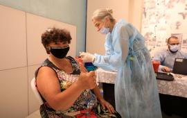 Pacjentka przyjmuje szczepionkę i pokazuje uniesiony kciuk.