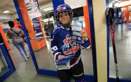 Chłopiec w stroju hokejowym reklamuje naukę jazdy na łyżwach