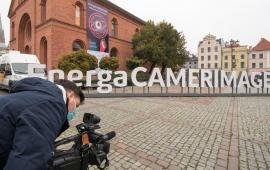 Napis EnergaCamerimage na Rynku Nowomiejski, na pierwszym planie operator kamery