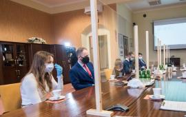 Pięcioro absolwentów siedzi przy stole, od pozostałych uczestnikow spotkania oddziela ich plastikowa ścianka