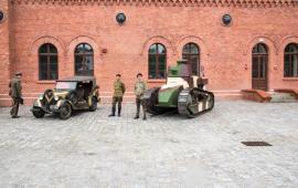Zabytkowe pojazdy wojskowe stoją na tle Muzeum Twierdzy Toruń.