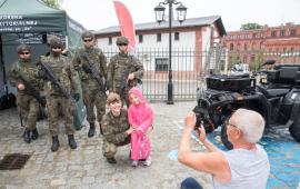 Dziewczynka pozuje z żołnierzami do zdjęcia.