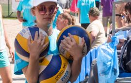 Na zdjęciu dziewczynka trzyma piłki do siatkówki
