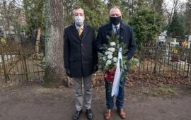 Zastępca prezydenta Paweł Gulewski i przewodniczący Rady Miasta Marcin Czyżniewski stoją z wiązanką biało-czerwonych kwiatów, przed złożeniem ich na grobie Wandy Szuman