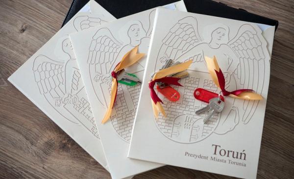 Na zdjęciu na stole leżą teczki Prezydenta Miasta Torunia i klucze