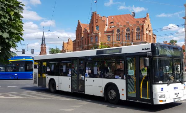 Na zdjęciu: autobus i tramwaj na tle Urzędu Miasta Torunia