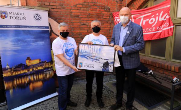 Na zdjęciu prezydent Torunia Michał Zaleski, prof. Ireneusz Sobota oraz Ryszard Kruk trzymają plakat filmu z podziękowaniami dla Gminy Miasta Toruń