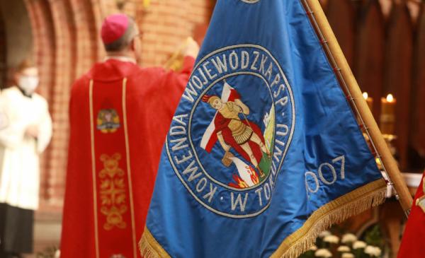 Na zdjęciu sztandar Komendy Wojewódzkiej PSP w Toruniu, w tle biskup odprawia mszę