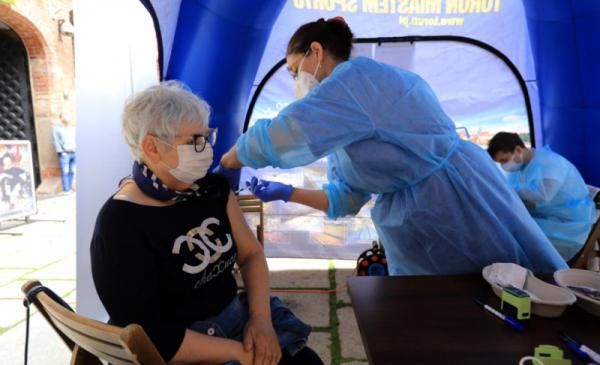 Na zdjęciu - pielęgniarka wykonuje szczepienie kobiecie