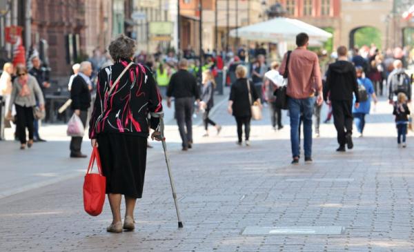 Na zdjęciu widać starszą panią, poruszającą się o kuli, niosącą zakupy w czerwonej torbie