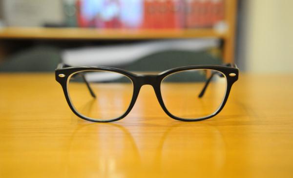 Na blacie biurka leżą okulary