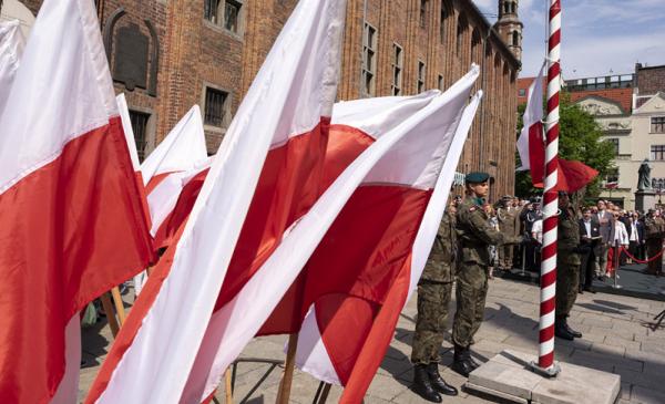 flagi państwowe i żołnierze pełniący wartę przed ratuszem