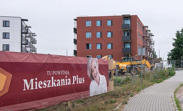 """widok bloku i baneru z napisem """"Tu powstają Mieszkania Plus"""""""