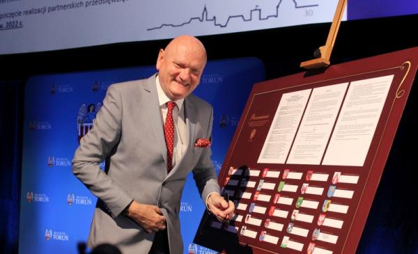 Na zdjęciu prezydent Michał Zaleski stoi obok podpisanego porozumienia