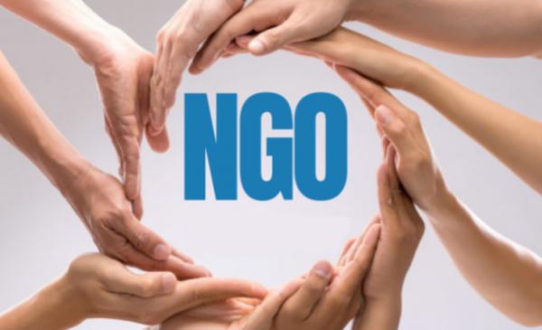Niebieski napis NGO otoczony splecionymi dłońmi.
