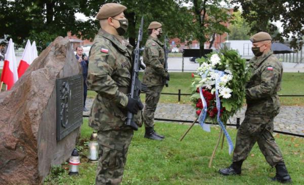 Żołnierze składają wieniec biało-czerwonych kwiatów pod obeliskiem