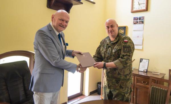 Prezydent Michał Zaleski wręcza list gratulacyjny odchodzącemu komendantowi Centrum szkolenia Wojsk Obrony Terytorialnej płk. Krzysztofowi Leszczyńskiemu