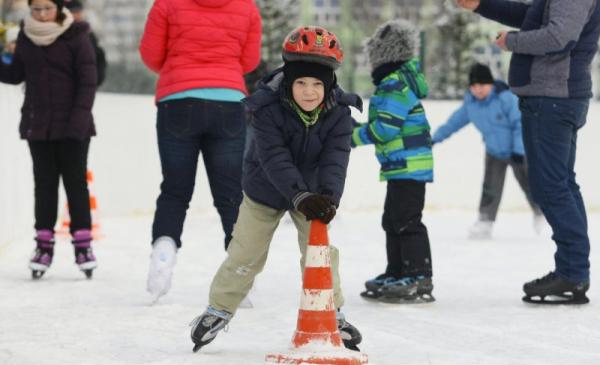 Na zdjęciu chłopiec na łyżwach na lodowisku trzyma się słupka