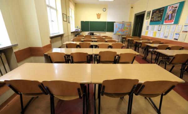 Na zdjęciu puste ławki i krzesła szkolne w klasie