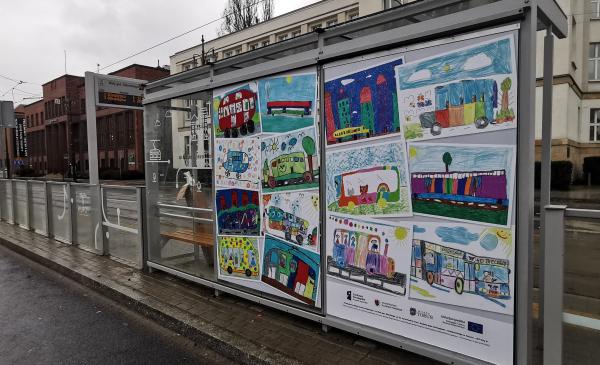Na zdjęciu wiata przystankowa z plakatem przedstawiającym prace plastyczne dzieci
