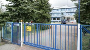 Na zdjęciu widać budynek Domu Pomocy Społecznej im. dr. Leona Szumana, na pierwszym planie niebieska brama