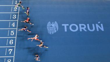 Widok na bieżnię w Arenie Toruń, startujących biegaczy i napis Toruń oraz herb miasta