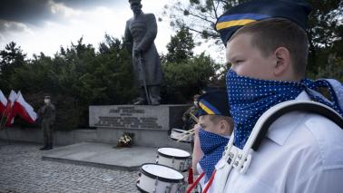Chłopiec dobosz na tle pomnika Piłsudskiego w Toruniu