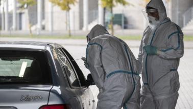 Na zdjęciu mężczyźni w kombinezonach pobierają wymaz osobie znajdującej się w samochodzie