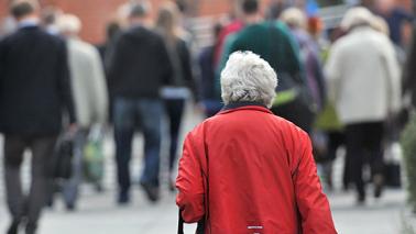 Starsza pani idąca ulicą Torunia