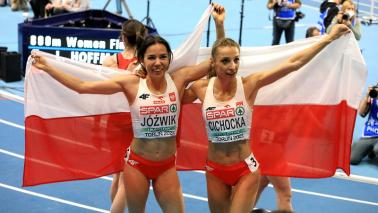 Uśmiechnięte Joanna Jóźwik i Angelika Cichocka z flagą narodową Polski