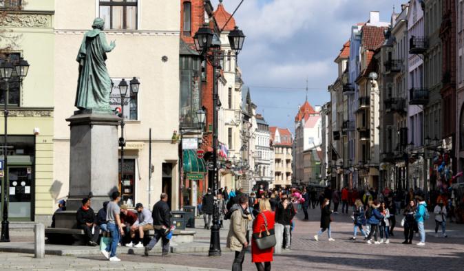 Turyści przy pomniku Kopernika, widok w stronę ulicy Szerokiej