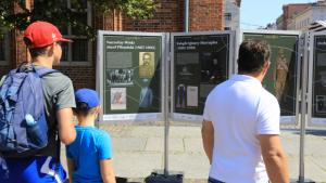 Mężczyzna i dwóch chłopców oglądają wystawę w Toruniu