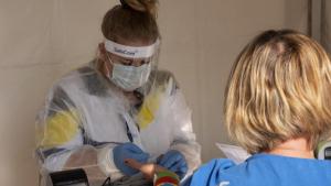 Na zdjęciu: lekarka w przyłbyci i maseczce pobiera krew od pacjentki