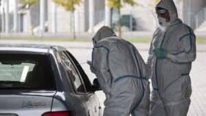 Na zdjęciu pracownicy medyczni w kombinezonach ochronnych pochylają się nad otwartym oknem samochodu, by wykonać wymaz