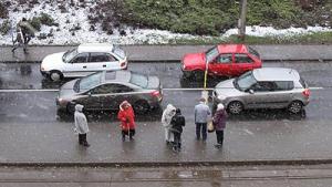 Pasażerowie stoją na przystanku tramwajowym, widać padający drobny śnieg, który od razu topnieje na ulicy