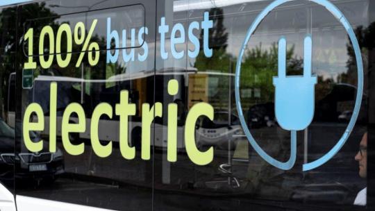 """Na zdjęciu szyba autobusu elektrycznego z napisem """"100 percent electric bus test"""""""
