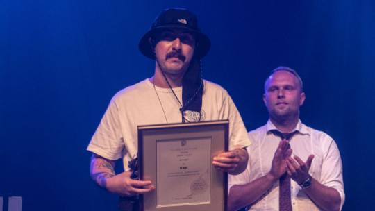 Na zdjęciu zdobywca tytułu DJ Roku, WRB. trzyma statuetkę oraz dyplom