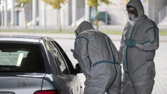 Medycy ubrani w białe kombinezony pochylają się nad otwartym oknem samochodu, aby pobrać wymaz siedzącej wewnątrz osobie