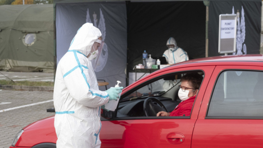 Na zdjęciu osoba w kombinezonie podaje płyn antybakteryjny kobiecie w samochodzie