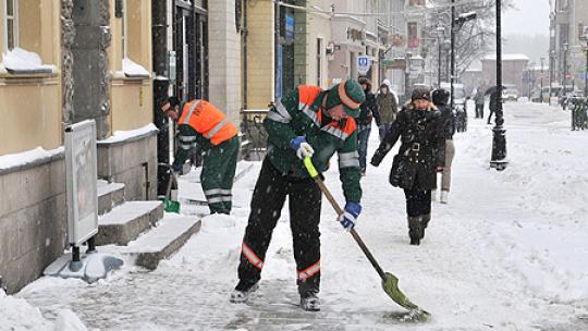 zdjęcie mężczyzny odśnieżającego chodnik