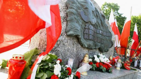 Kwiaty i flagi biało-czerwone pod obeliskiem Ku czci Żołnierzy Armii Krajowej na placu Rapackiego