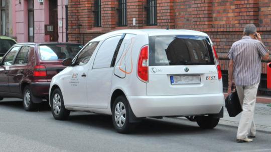 Auto stojące na ulicy. Obok przechodzi mężczyzna rozmawiający przez telefon.