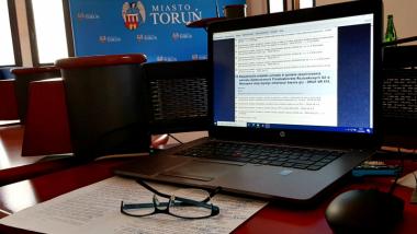 22. sesja Rady Miasta Torunia - ekran monitora na tle banera Toruń