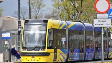 Na zdjęciu żółto-niebieski tramwaj stoi na przystanku