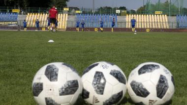 Na zdjęciu widać trzy piłki do piłki nożnej na zielonej murawie stadionu