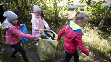 Na zdjęciu: dzieci zbierające śmieci do worka